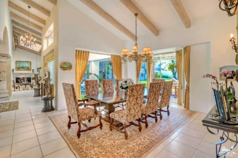 The white shed ceiling has exposed wooden beams that support an intricate chandelier that matches the chic quality of the dining chairs and their patterned cushions as well as the beige patterned area rug over the white tiles of the flooring.