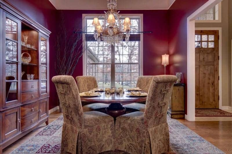 The dark reddish purple tone of the walls are augmented by the warm yellow lights of the table lamp and the matching chandelier. This is also brightened by the natural lights coming in from the tall windows onto the floral patterns of the slipcovers and area rug.