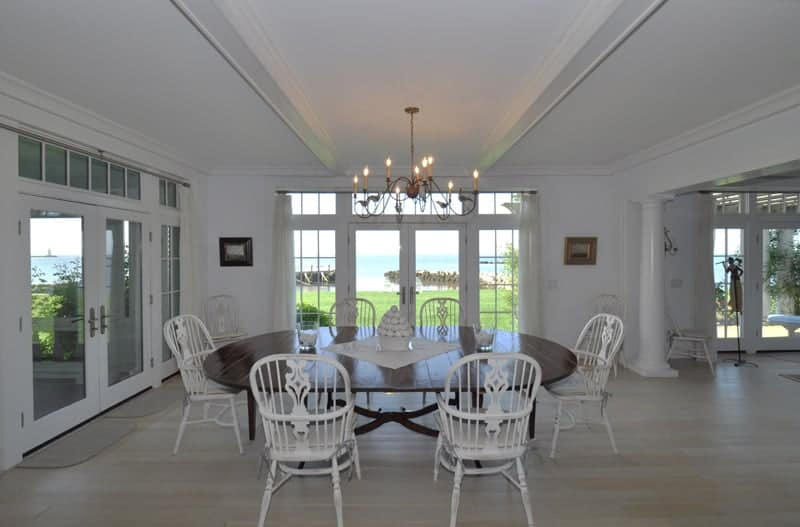 The classic white wooden chairs that stand out against the dark wooden elliptical dining table matches with the light hardwood flooring, white walls and white ceiling that has exposed wooden beams flanking a thin chandelier.