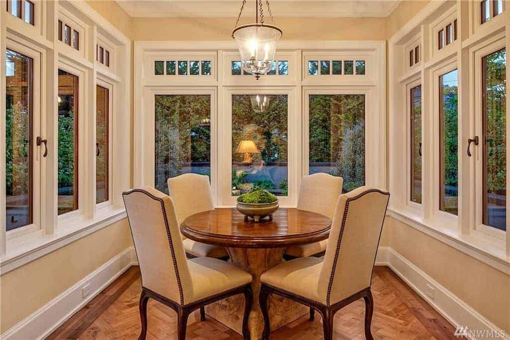 The beige cushions of the dining chairs are a perfect match for the beige walls. These parts are barely seen due the dominance of the white tall windows surrounding the medium-sized dining room. The hardwood flooring that has a herring bone pattern matches the wooden round table.