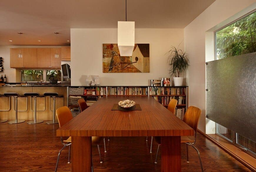 The beige wall above the beautiful bookshelf is adorned with a painting of a bird and its birdhouse that has various shades of brown. This painting sets up the brown theme of the dining area that has a brown wooden rectangular table and brown modern chairs over a hardwood flooring.