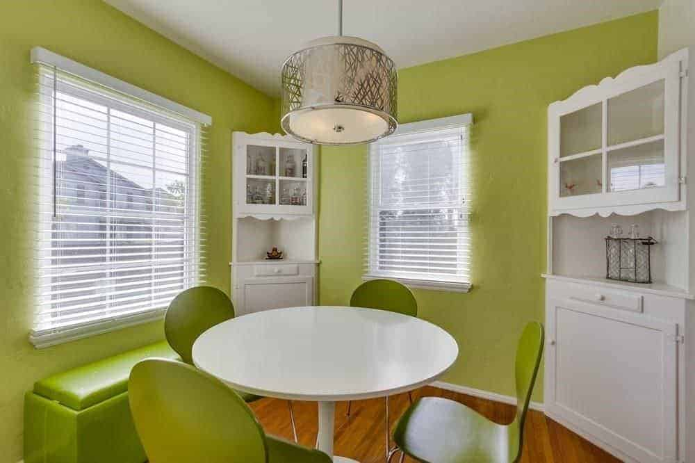 The light green walls that are brightened by the couple of windows with white blinds are a complement to the the dark green modern chairs that surround the white modern round dining table. It also matches the green leather cushioned bench by the window.