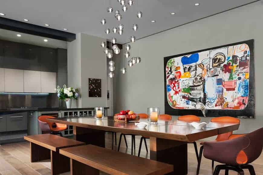 This informal dining room has a friendly and quirky demeanor with its colorful painting on the light gray walls and small silver spherical pendant lights hanging from the gray ceiling. This colorful scheme is matched by the orange modern dining chairs of the wooden table and its wooden benches.