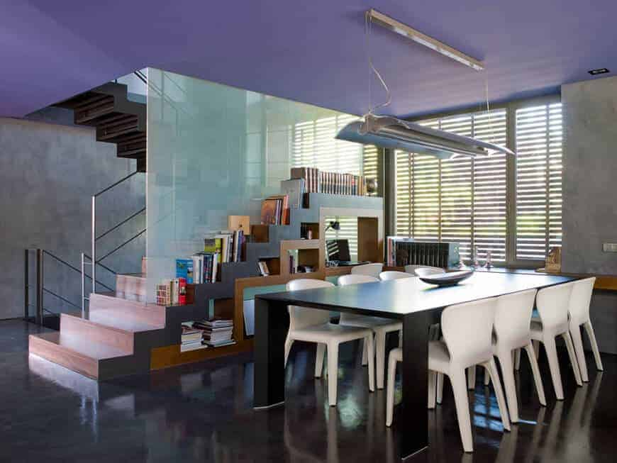 This modern dining area by the stairs has white modern chairs that stand out against the black modern dining table and black industrial-style flooring that matches well with the industrial-style fluorescent light hanging from the ceiling.