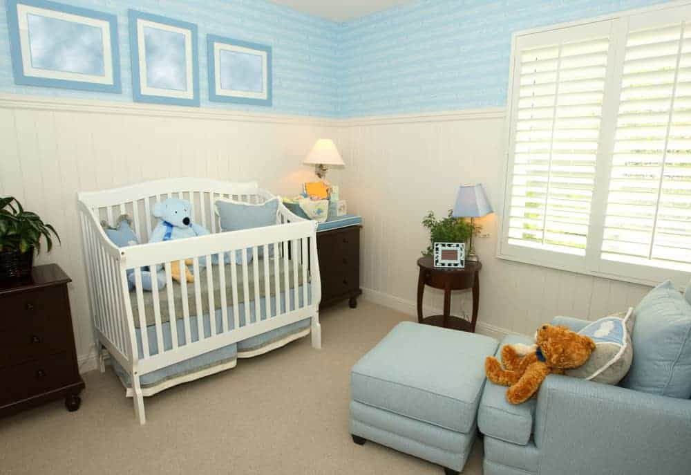 A blue armchair with matching ottoman faces the skirted crib in this nursery with carpet flooring and white beadboard lower wall accented with blue framed artworks.
