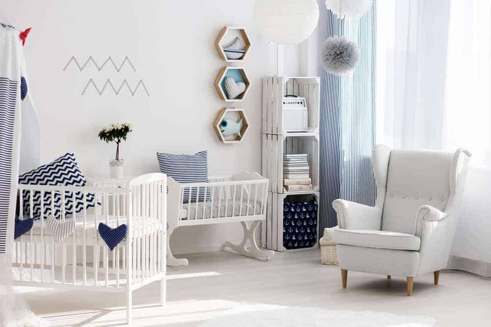 A cool shared nursery with rustic shelving and hexagon shelves mounted on the white wall. It includes white cribs and a gray wingback chair lighted by round pendants.