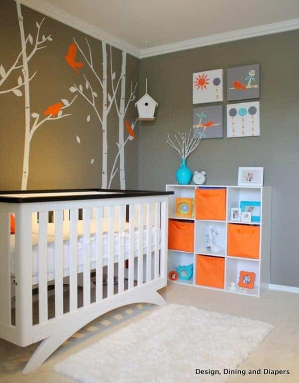 A tree and bird wall sticker sets a cute backdrop to the white crib in this nursery showcasing a shaggy area rug and open shelving filled with frames and orange boxes.