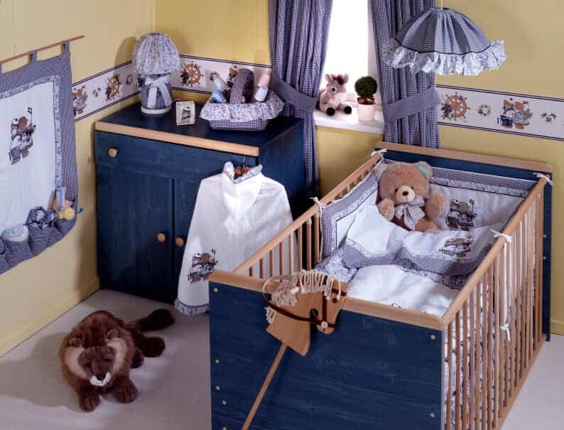 A teddy bear themed nursery with a wooden crib and denim blue cabinet placed against the yellow walls. It has carpet flooring and a glazed window covered in checkered draperies.