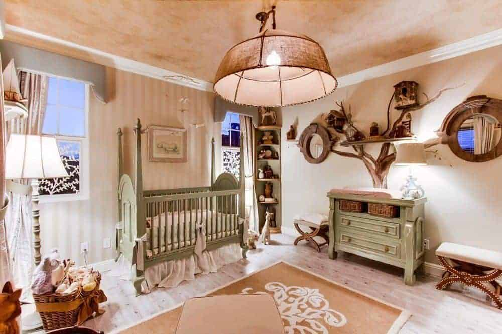 Warm nursery illuminated by an oversized dome pendant that hung over the beige printed rug on hardwood flooring. It has green four poster crib and cabinet designed as a tree along with a floating shelf and mirrors.