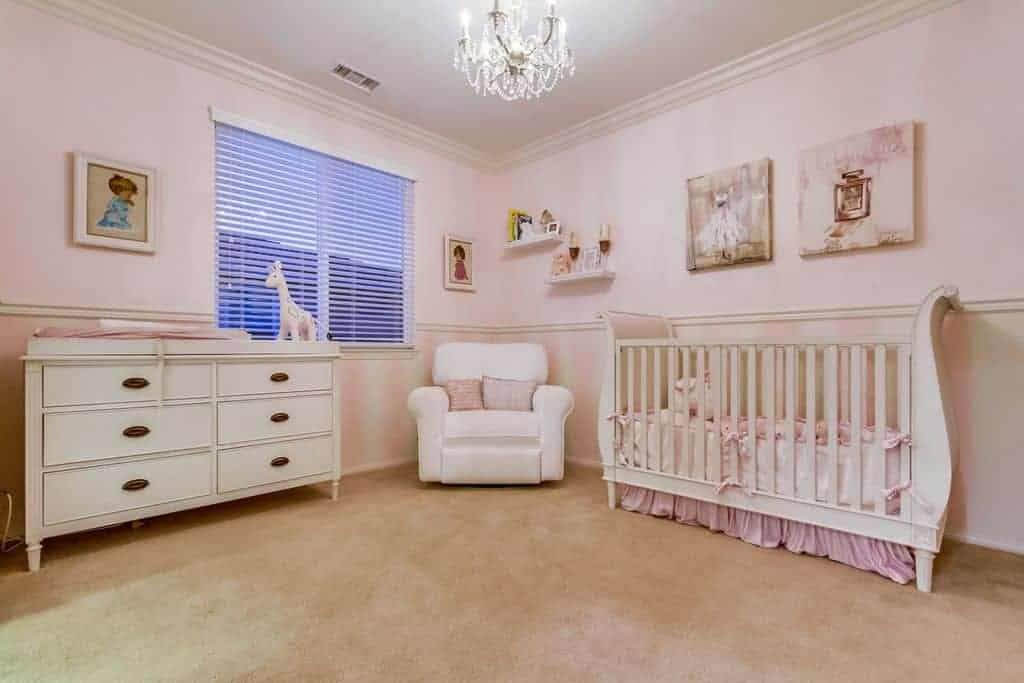 Charming wall arts hang above the skirted crib in this light pink nursery with white drawer chest and armchair lighted by a crystal chandelier.