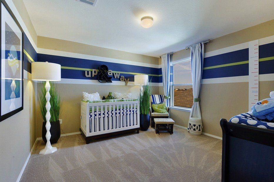 Stylish nursery with beige armchair and white crib over carpet flooring. It is illuminated by gorgeous white floor lamps and flush mount light bringing a warm and cozy ambiance to the room.