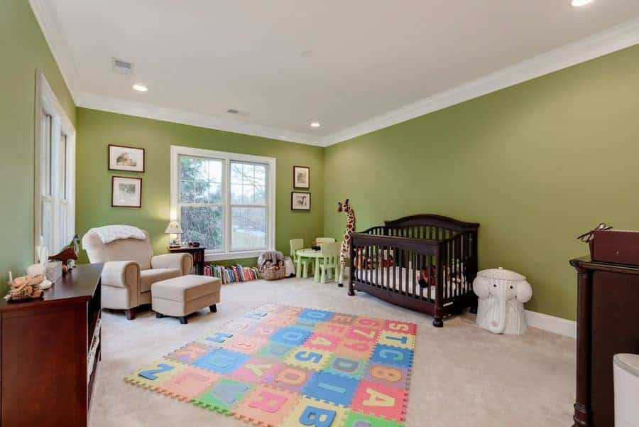 A large nursery with green walls and gray carpet flooring topped by an alphabet puzzle mat. It has smooth armchair with matching ottoman and a dark wood crib next to the small table and chairs.