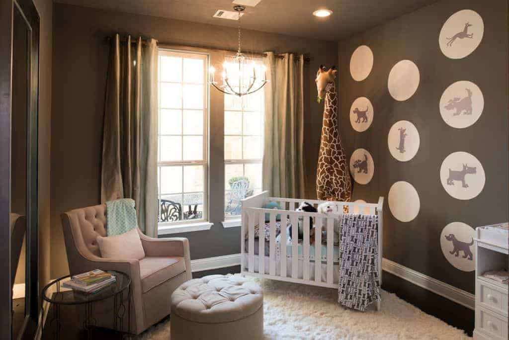 Gray nursery decorated with a candle chandelier and a large giraffe plush toy that sits behind the white crib on a shaggy area rug. It has full height mirror and a tufted armchair accompanied by a matching round ottoman and glass top side table.