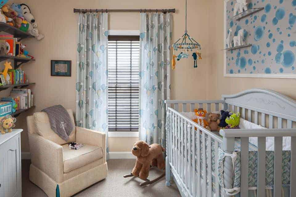 A cute baby mobile hangs over the gray crib in this beige nursery offering a skirted armchair and wooden floating shelves filled with books and toys.