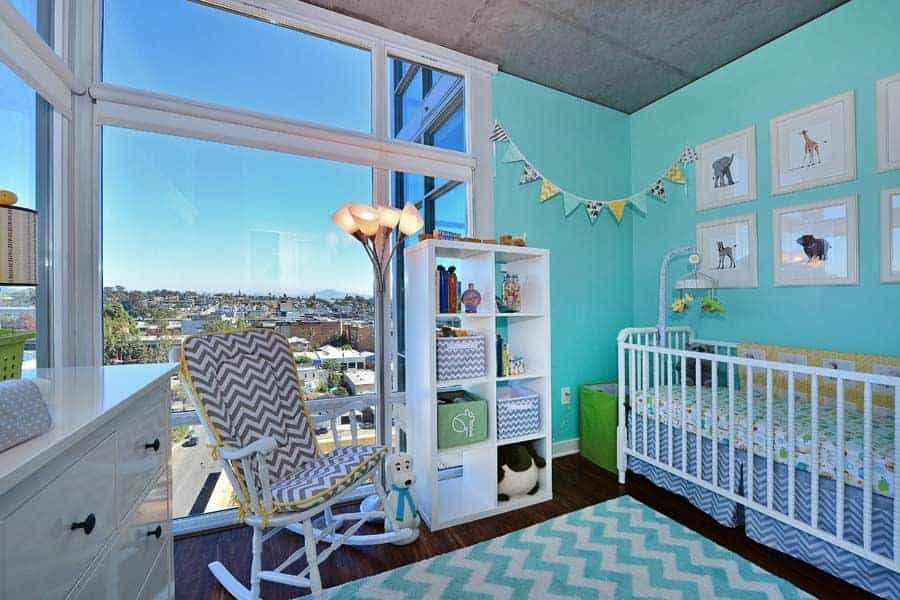 This nursery is decorated with garland flag and animal artworks mounted above the skirted crib. It has a chevron rug and armchair against the full height glazing overlooking the incredible city view.