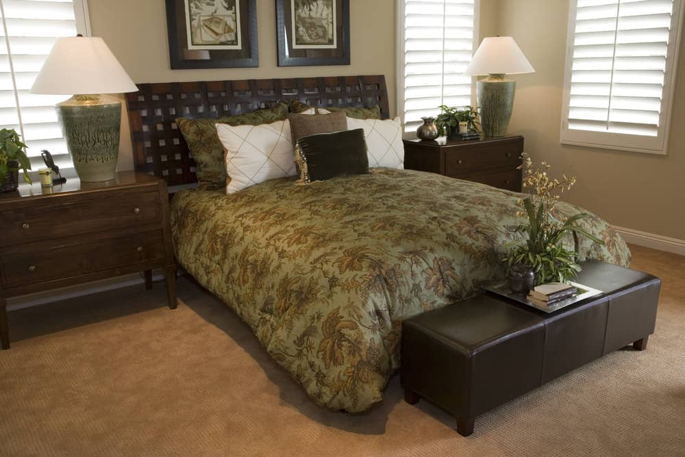 This bedroom offers a classy bed setup lighted by two table lamps set on top of bedside cabinets. The room also has carpet flooring.