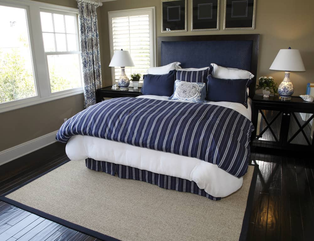 A focused shot at this primary bedroom's navy blue bed setup with a brown area rug on top of the hardwood flooring.