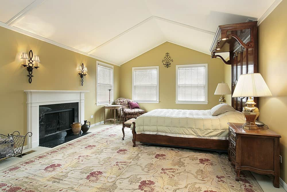 Large primary bedroom featuring a vaulted ceiling and a large classy area rug. It has a luxurious large bed along with a large fireplace lighted by wall lights.