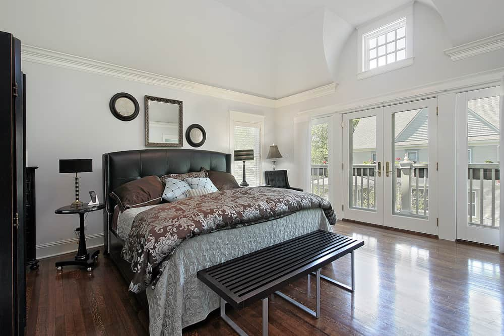 A spacious primary bedroom featuring white walls, hardwood flooring and a tall ceiling. The room offers a large classy bed lighted by two table lamps.