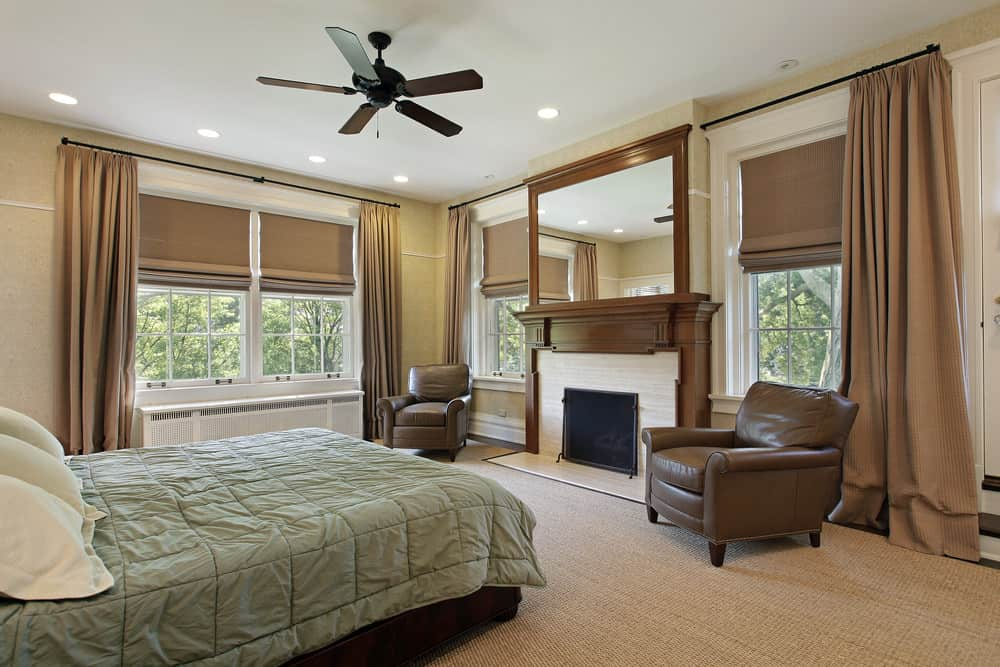 Primary bedroom featuring brown carpet flooring along with brown window curtains. The room offers two brown leather seats along with a fireplace.