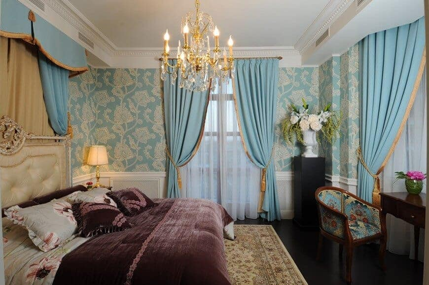 Primary bedroom with elegant walls and a glamorous chandelier lighting up the place. The room offers a nice classy bed.