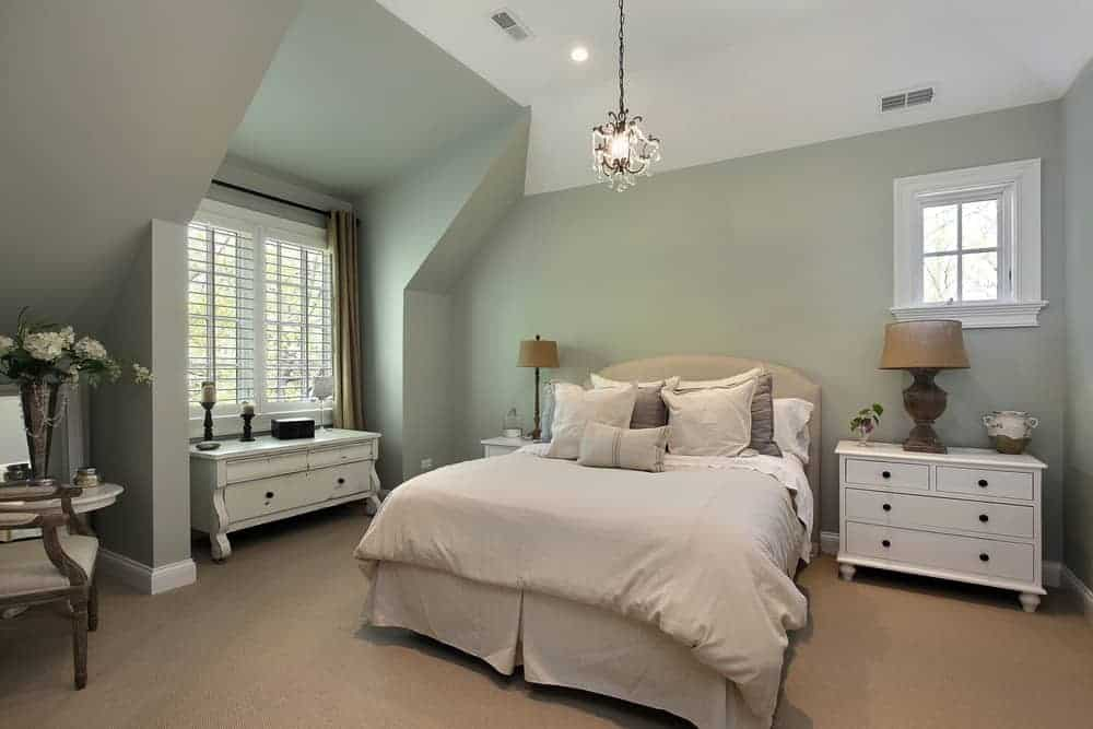 Country style primary bedroom featuring carpet flooring and green walls, along with a tall ceiling. The room offers a nice bed lighted by a fancy pendant light.