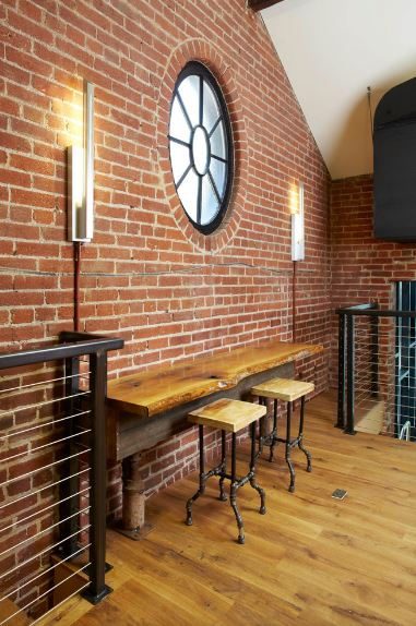 The red brick wall of this industrial-style foyer has a built-in table with water pipes as legs. This is paired with a couple of wooden stools with pipes for legs as well. This is given a nice background of a circular window flanked by modern wall lamps.