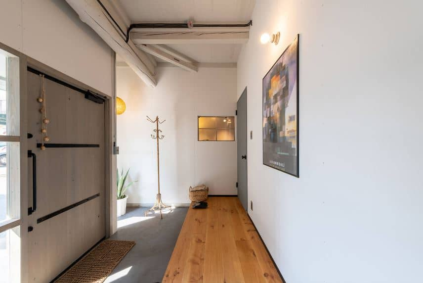 This charming foyer has a large wooden door with side lights. This is complemented by the gray concrete flooring lower than the hardwood flooring on the white wall across from the door that is adorned with a colorful poster lit with a light bulb.