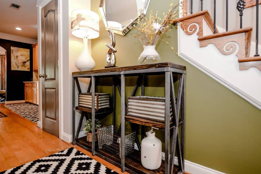 This charming foyer has an industrial-style console table with gray metal rods that pairs well with the wooden shelves filled with decors and supports a table lamp above that casts yellow light on the green wall that complements the hardwood flooring and the steps of the stairs.