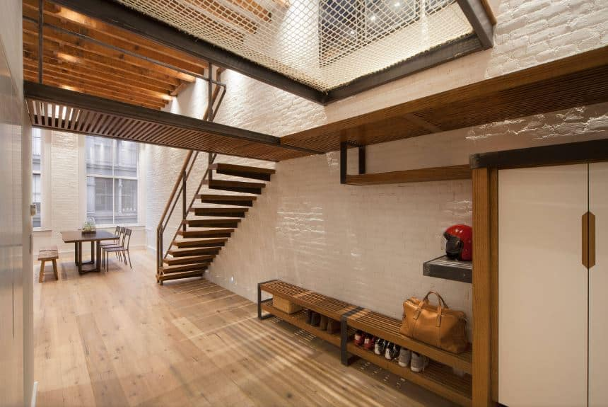 This industrial-style foyer has metal beams that support cat walks that would fit in a factory. This matches with the long wooden bench against the textured stone white wall with a lower shelf that serves as a shoe rack while the ones above are for helmets and hats.