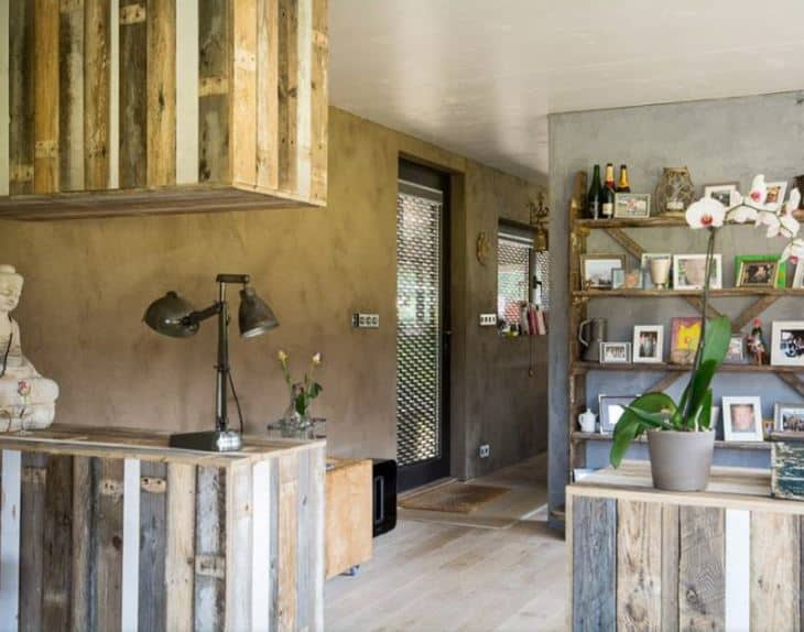 This foyer is a nice fusion of industrial-style elements and farmhouse-style elements. This foyer has a glass door with a peculiar industrial-style design to it. The door opens to a foyer with light hardwood flooring and industrial-style concrete walls that are complemented by various wooden structures.