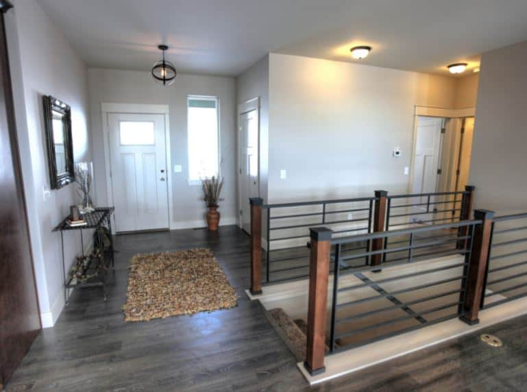 This simple industrial-style foyer has a white wooden door with a glass panel on it matching the window beside it. This door contrasts the gray hardwood flooring that complements the industrial-style semi-flush mount light and the dark iron console table on the side.