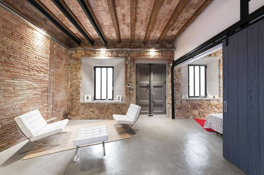 This industrial-style foyer has a lovely sitting area on the side that stands out against the red brick walls, stone walls and ceiling that has exposed wooden beams. All these earthy and textured surfaces are contrasted by the stark white modern sofas with a tufted finish.