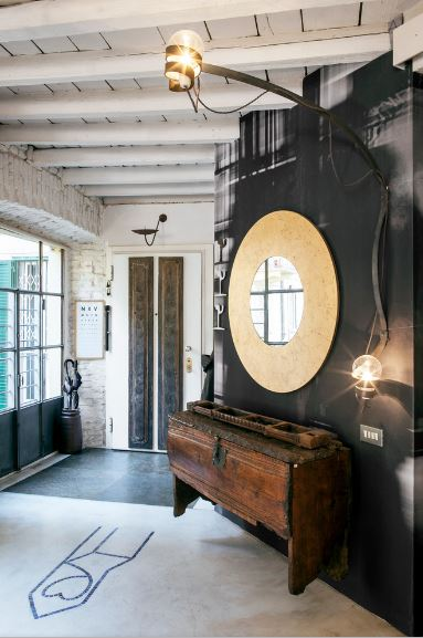 This foyer is almost filled to the brim with small details that solidify its industrial-style quality. It has a white wooden ceiling with exposed wooden beams that bleed into the black wall of the wall-mounted round mirror above a floating old wooden cabinet lit with a light bulb with exposed wires.