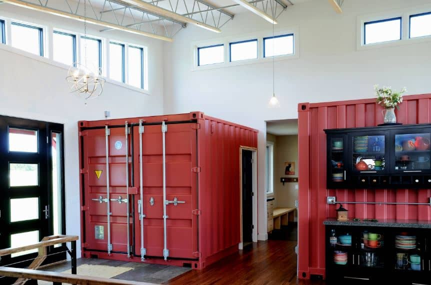 The main door of this industrial-style foyer is a stylish dark wooden door with glass panels matching the side lights. Upon entry, the guest's attention is immediately pulled by the couple of truck containers fitted into the house to be part of the decor and the house as a couple of rooms with doors.