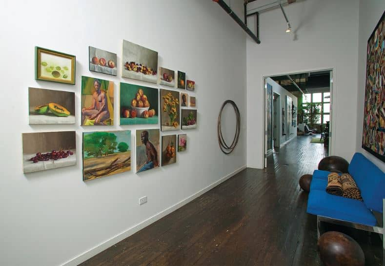 This hallway-like foyer has a dark hardwood flooring that matches the spherical decors beside the blue modern sofa that stands out against the white walls and ceiling with exposed pipes. Across from the sofa is a collection of wall-mounted paintings that bring color to the industrial-style foyer.