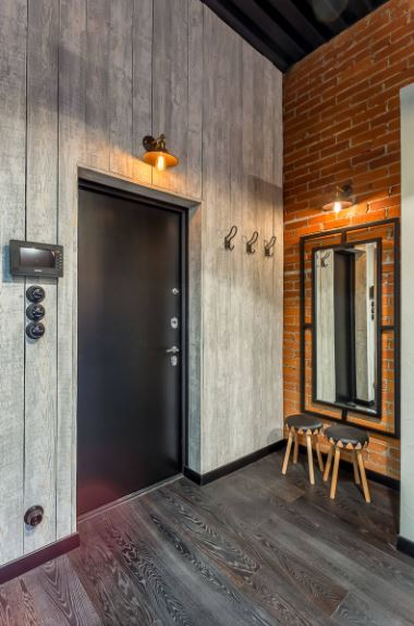 The black main door is lit with a warm yellow light by the industrial-style wall lamp above the door. This matches with the wall lamp above the mirror that is mounted on the adjacent wall that is made of red bricks and paired with a couple of small wooden stools.