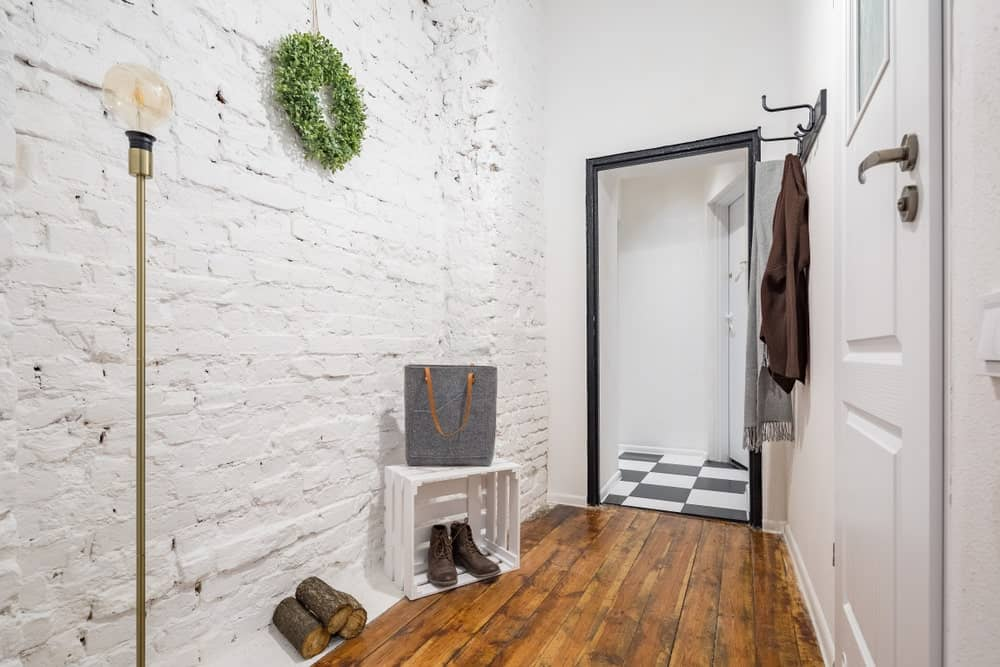 Industrial-style foyer with whitewashed exposed brick wall, a floor lamp, and hardwood flooring.