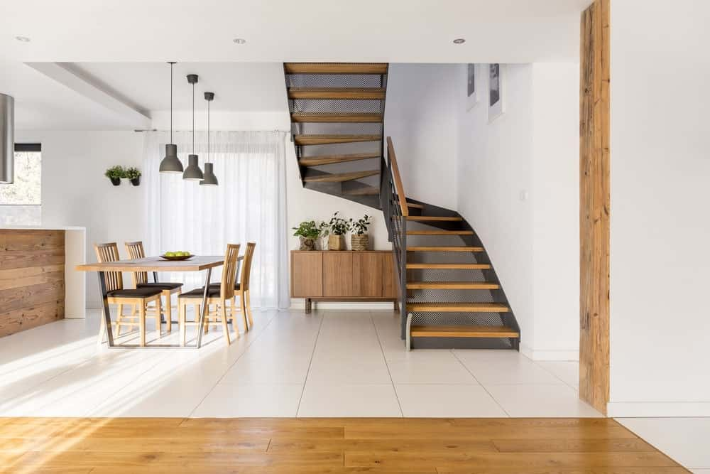 This foyer has a clear view of the dining room by stairs that has the same industrial-style to it as the dining set. There is also a console table against the white walls that pairs well with the flooring tiles. This transitions to hardwood flooring as it nears the foyer.
