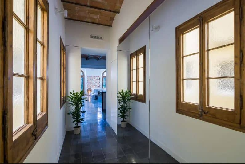 This narrow hallway-like foyer has a large seamless mirror on the right side that gives it an illusion of being bigger than reality. It has industrial-style gray flooring tiles that contrast the white walls that has a pair of wood-framed windows with frosted glass.