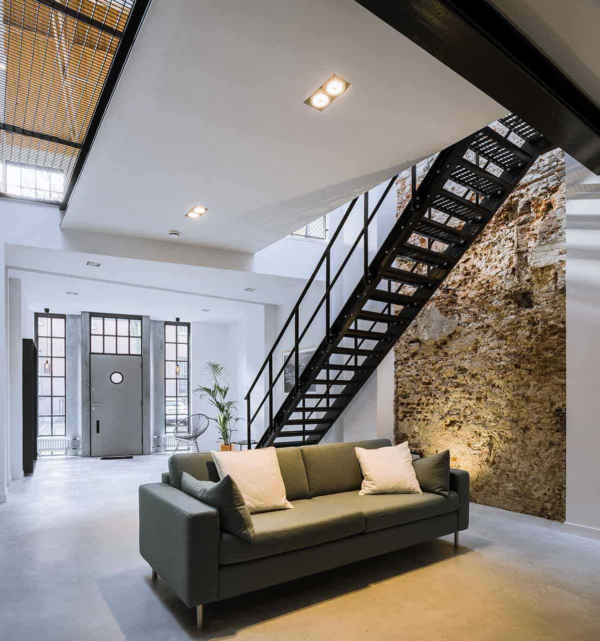 This interior view of the house shows the foyer as you enter the main door. It has a white interior with simple white walls, ceiling and industrial-style flooring. This makes the black mudroom and metal stairs stand out as well as the potted plant in the corner.