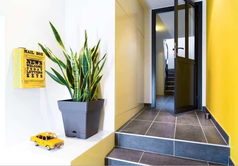 This foyer has a cheerful welcome for the guests with its yellow wall that matches with the mailbox and the taxi decor beside the potted plant. This yellow wall is contrasted by the matte industrial-style flooring as well as the black wooden door.