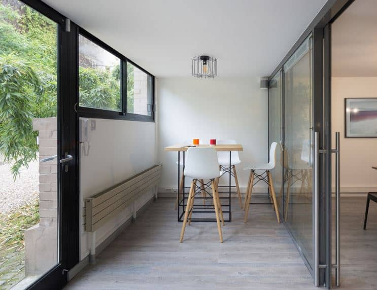 The glass main door leads to this small foyer that has a sitting area with white stools around an industrial-style wood-top table under a caged light bulb from the white ceiling. Along the wall is a folding bench for additional seats of the waiting guests.