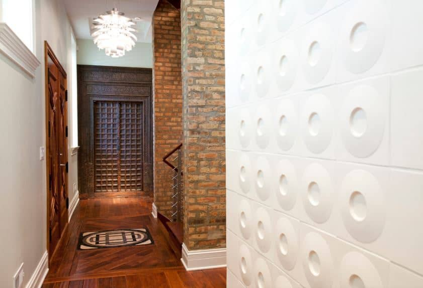 The intricate and elegant wooden main doors match with the hardwood flooring topped with a peculiar pendant light that brightens the foyer. Across from the door is the staircase that has two large pillars made of bricks on either side of it.