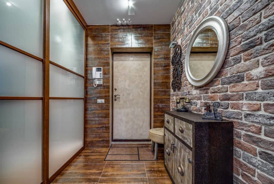 This foyer is dominated by the earthy hues of the brick walls and the brown tiles of the flooring that extends to the wall framing the main door. Adjacent to this is the brick wall that has a wooden cabinet and mirror. Across from this is a frosted glass wall.
