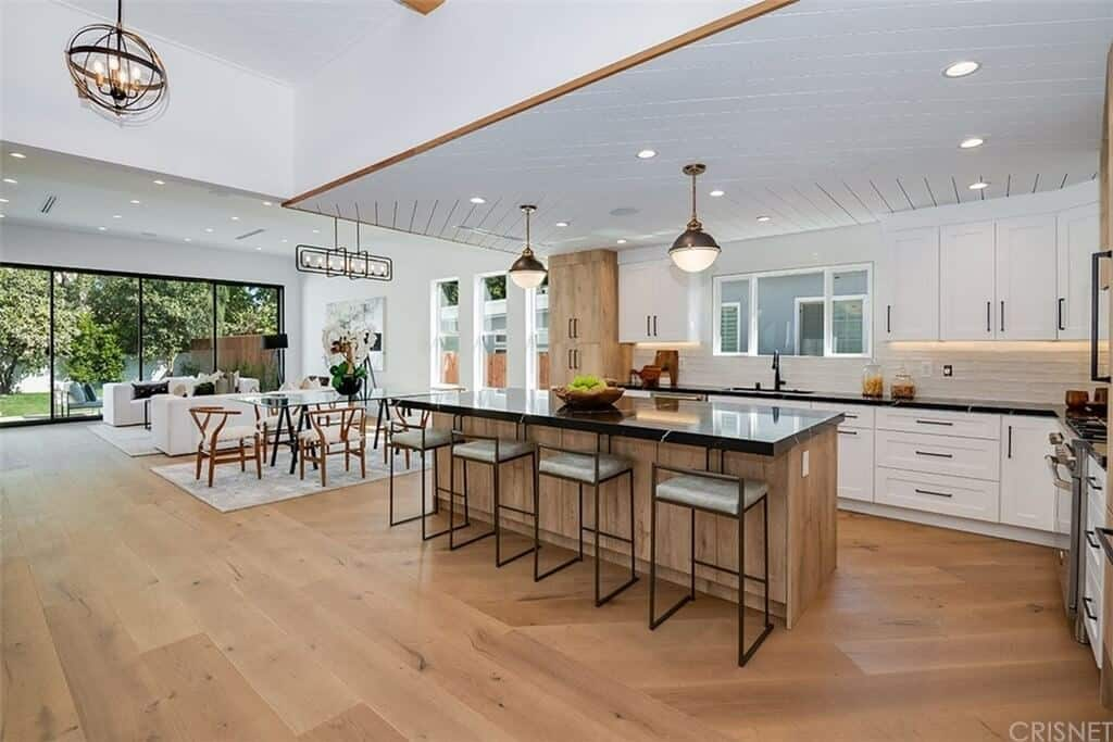 Modern farmhouse open concept space featuring white ceiling and walls and hardwood flooring.