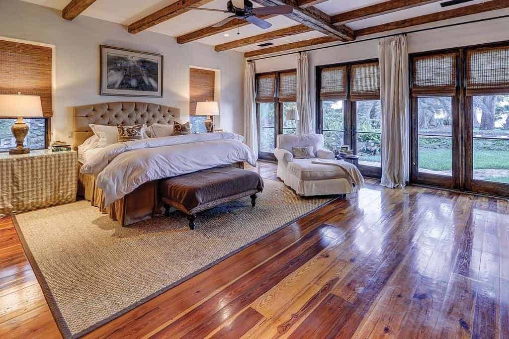 Cozy bedroom with white skirted chaise lounge and a beige tufted bed flanked by checkered nightstands and traditional table lamps. It has a wood beam ceiling and glass paneled windows covered in wicker roman shades.