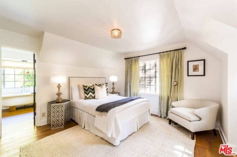 Large primary bedroom featuring hardwood flooring and white walls. The room has a comfy double-sized bed along with its own bathroom featuring a freestanding tub.