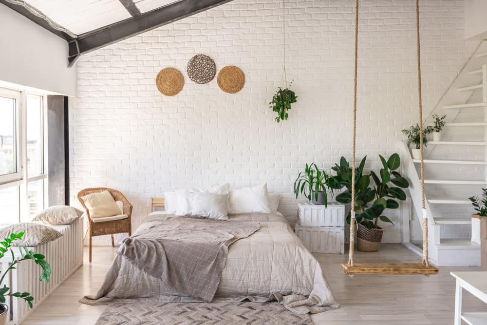 White brick accent wall adds texture in this tropical bedroom featuring a rope swing and comfy bed that sits on the gray chevron rug over light hardwood flooring.