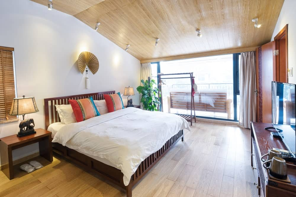 Cozy primary bedroom with a wooden bed and nightstands topped with elephant table lamps. It is illuminated by white track lights that are mounted on the vaulted ceiling clad in light wood planks.